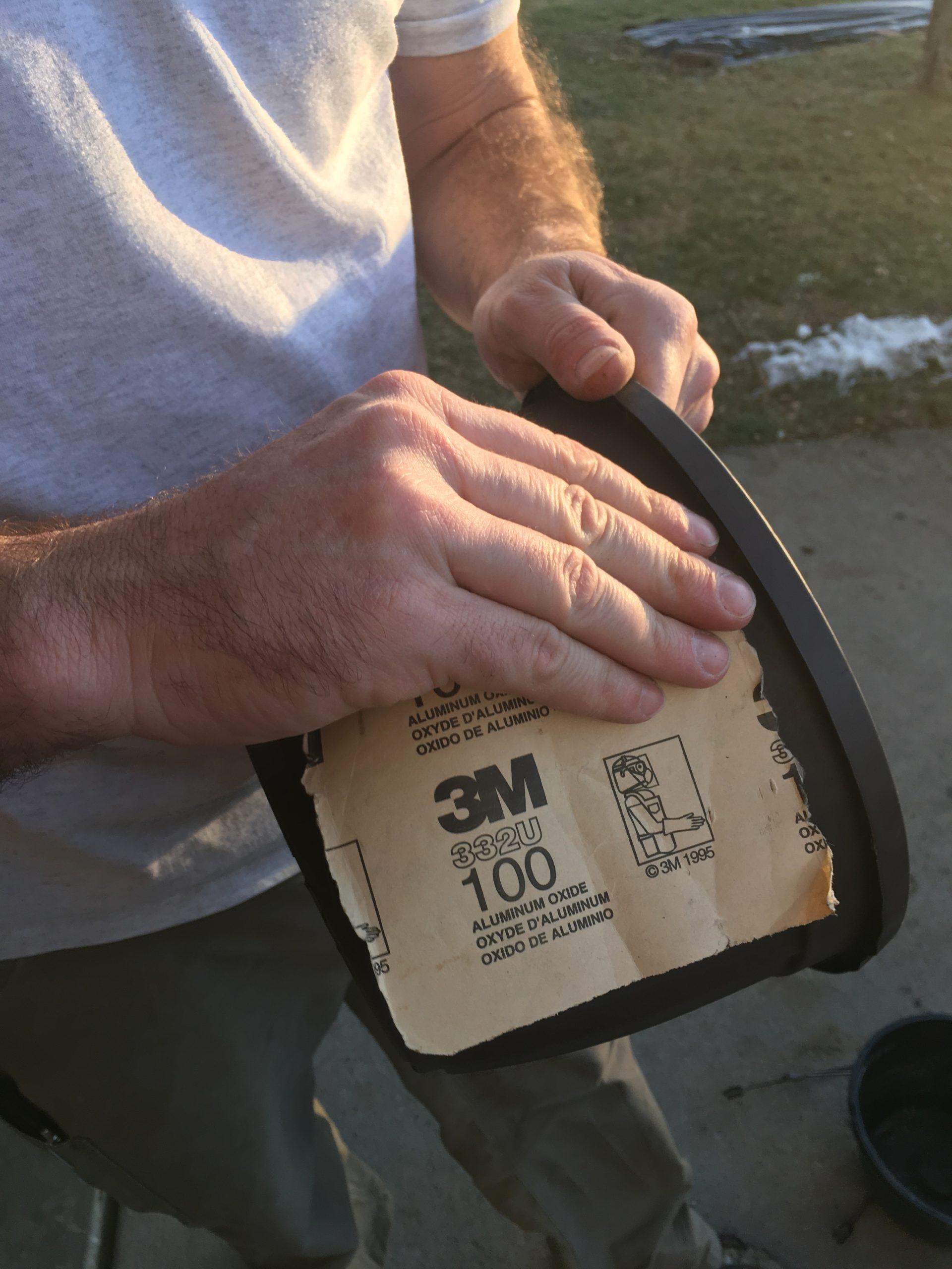 Poncage du pot en plastique avec du papier de verre.