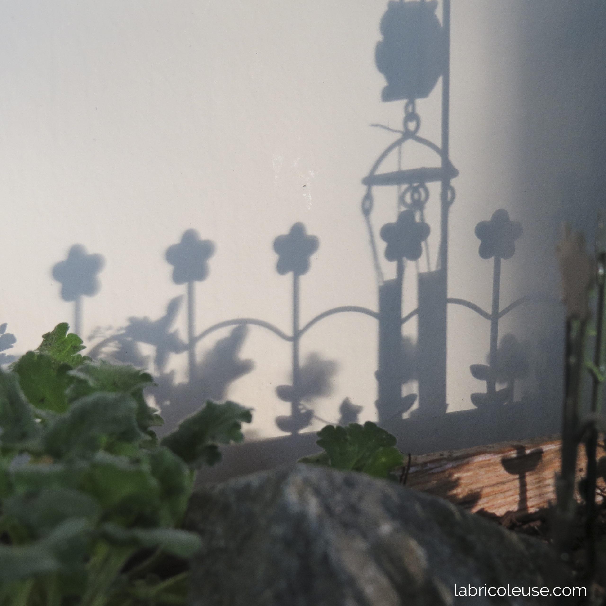 Ombre d'une barrière fleurie et d'un carillon contre un mur blanc.